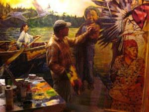 David Gilsvik works on one of the murals at the Grand Portage National Monument Heritage Center.