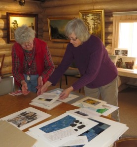 Ellen Stubbs and Mary MacDonald sort through the artwork submitted by art students at ISD 166.