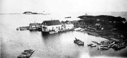 Historical fish houses, west side of the harbor.Note that the west breakwall has not been built yet, which would date this photo to somewhere between 1886 - 1901 (most probably the late 1890's). Photo from the John Wood Collection.