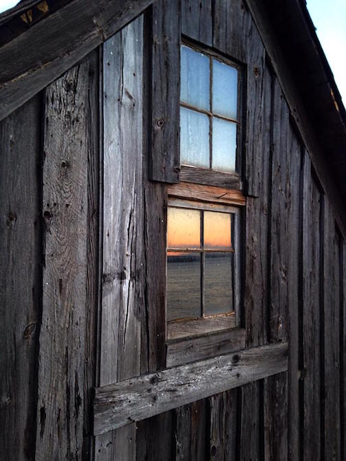 Sunset through the window of the shack on Stoney Point by Mark Subialka.