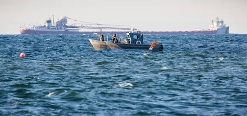 Working Superior -- Harley Tofte and the Dockside Fish Market crew tending nets as the Cason J. Callaway passes in the distance outside the Grand Marais Harbor.