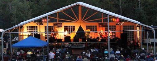 Musicians perform under a big tent at the Radio Waves Music Festival.