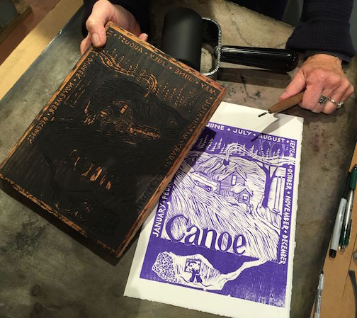 "Betsy Bowen shows the first inking of a print of ""Antler, Bear, Canoe's"" cover from the original woodblock. Jim Sannerud helped Bowen adjust the thickness of the block so it would fit on her press. Copies of the exclusive print will be available."