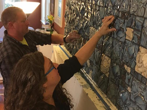 Melissa Wickwire and James Coleman install Wickwire's tiles above a fireplace in a Duluth residence.