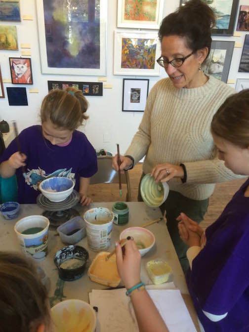 Great Expectations teacher Suzy Schwieg shows a student how to paint a bowl at the Grand Marais Art Colony. The class painted 25 bowls this week that will be donated to the Empty Bowls fundraiser Nov.10.