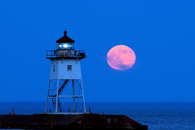 Strawberry Moon over the Grand Marais lighthouse by Kathy Gray Anderson.