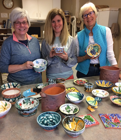 Hard work pays off! Pottery students Kathy Reeves, left, Priscilla Beck and Ann Mershon show off the work they created in the Pots of Painting class at the Grand Marais Art Colony,