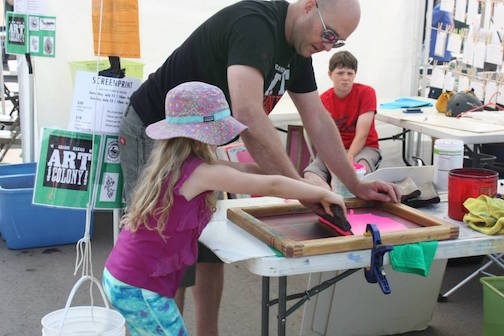 Mike Swindlehurst helps a youngster print her own T-shirt at the Grand Marais Arts Festival. (File photo courtesy of the Grand Marais Art Colony.