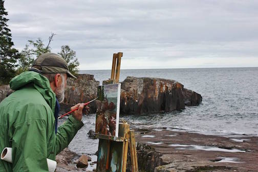 Plein air painter David Gilsvik painting a canvas on the rocks at Artist Point. Plein Air Grand Marais starts on Friday.