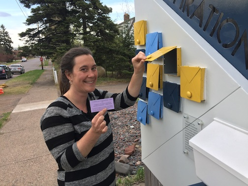 "Grand Marais Art Colony director, Amy Demmer, checks out one of the ""inspirations"" snuggled into a box in Greg Mueller's sculpture on an outside stairway at the Art Colony."