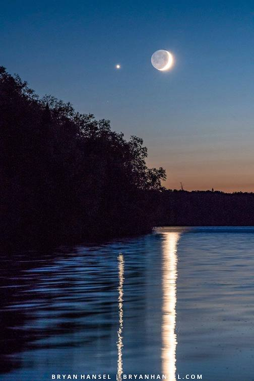 The setting crescent moon and Venus over Elbow Lake by Bryan Hansel.