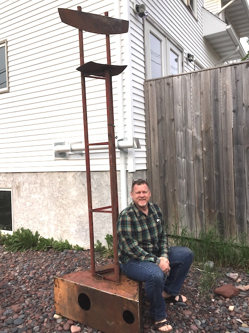 "Jim Sannerud and his ""High Chair,"" which was briefly on display outside the Art Colony until he took it home."