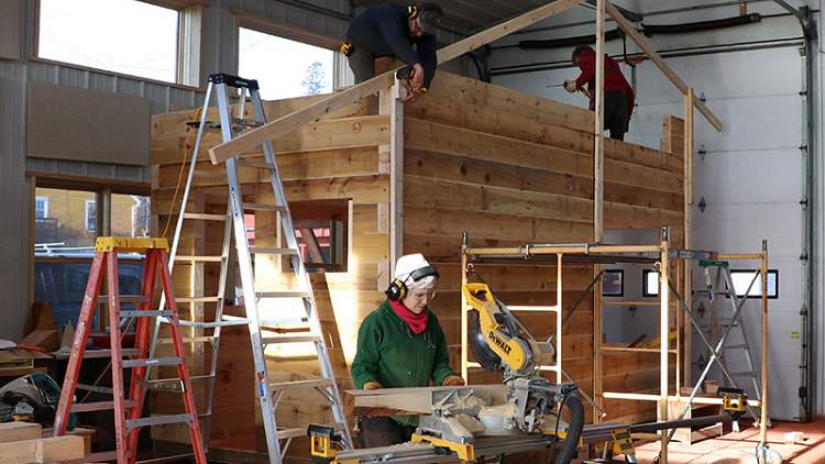 Angela Robbins works on the Tiny House being constructed in the Boat Barn at North House. It is finished and will be on-view on Friday.