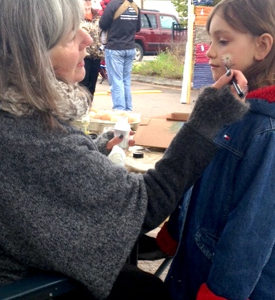 Cilla Walford paints a little flower on a customer's cheek at the Cook County Market last Saturday.