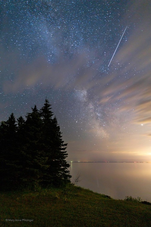 Competing night lights and a Perseid meteor by Mary Anne Pfitzinger.