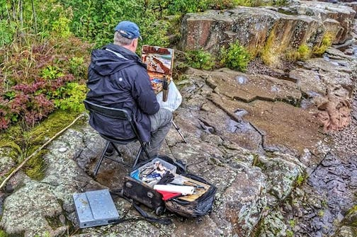 Bob Upton works on a painting for the Grand Marais Plein Air. Photo by Don Davison.
