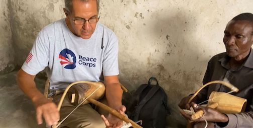 Bill Hansen takes a turn on learning to play   the khyihilili. a traditional fiddle in Uganda.