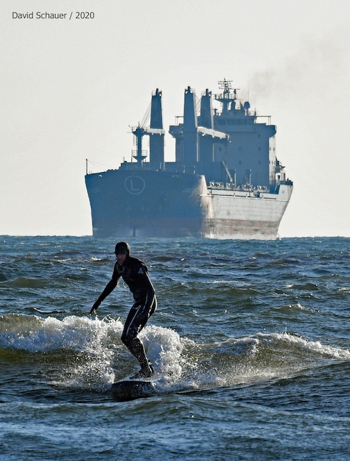 The St. Clair lining up for the Duluth Canal as the surfer rides the breakers. Photograph by David Schuauer.