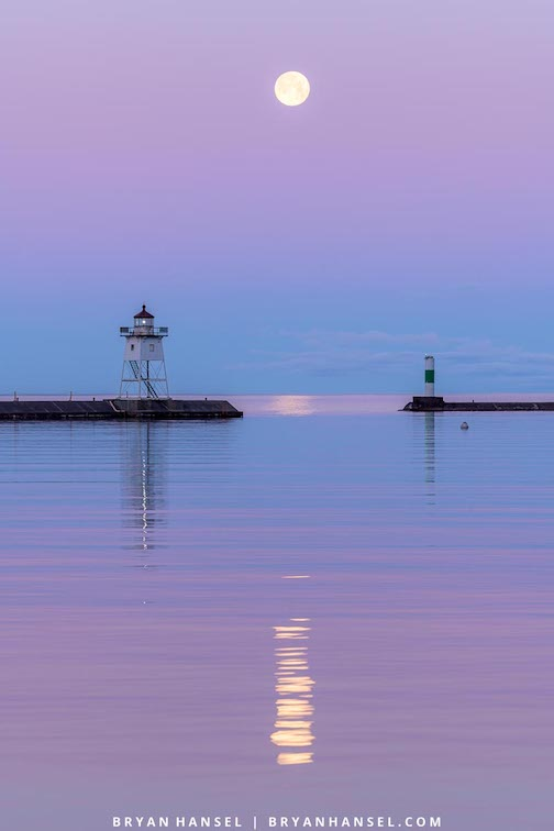 Full Strawberry Moon over the Grand Marais Harbor by Bryan Hansel.