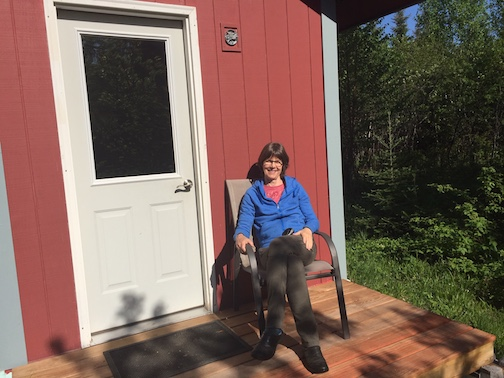 Kay Grindland in front of her writing shed.
