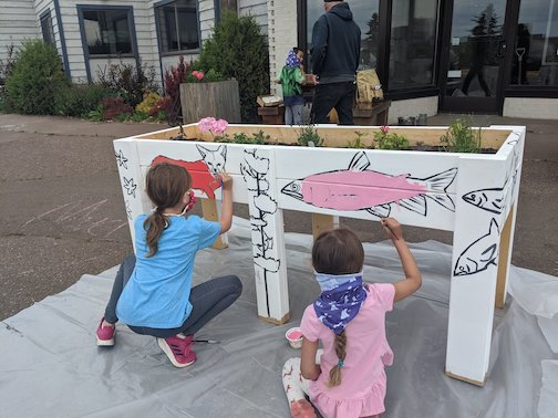 YMCA Summer Camp youth paint Tim Young's illustrations on flower boxes in front of the Hungry Hippie and Studio 21.