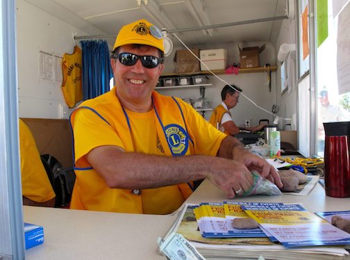 The Grand Marais Lions Club could set up a fishburger stand in Harbor Park on Friday and Saturday. Here, Carah Thomas Maskell caught Lions Club member Pete Kavanaugh serving up a fishburger in years past.