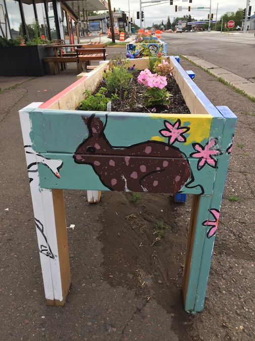 The kids from the Y's summer camp have finished painting the flower boxes in front of  Hungry Hippie Tacos.