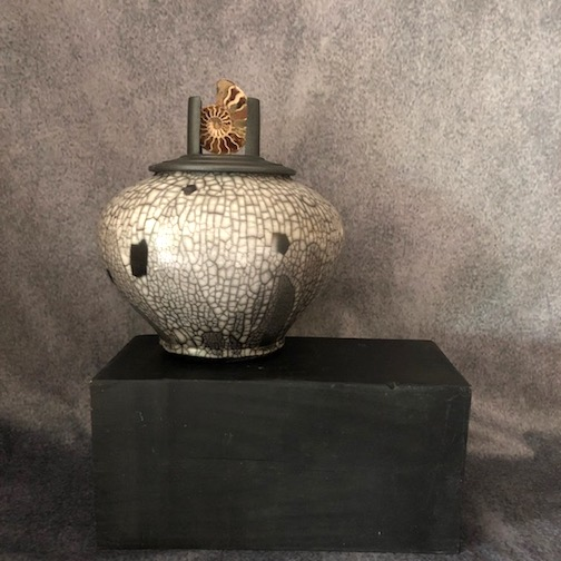 Naked Raku, porcelain urn with ammonite fossil embedded in lid by Maggie Anderson.