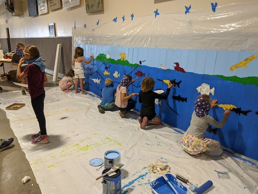 Young artists at work. Children from the Y Camp paint fish on the mural that will be installed at the playground at the Cook County Community Center.