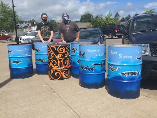 Ole Sorenson, left, and Sam Zimmerman stand beside the trash barrels they painted that will be set up around the City of Grand Marais, thanks to a grant from the Great Lakes Project.