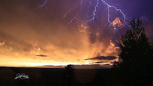 Lightning at sunset by Jamie Rabold.