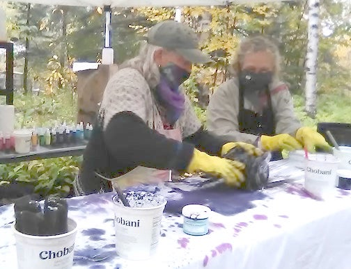 Weaver Julie Arthur dyes a scarf outside with a customer last week. She is offering the opportunity for a small f