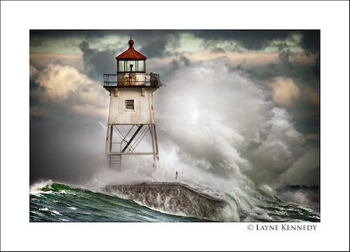 Lake Superior pounds the Grand Marais Lighthouse by Layne Kennedy.