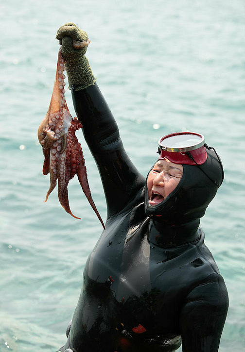 A Soutn Korean fisherwoman holds up her catch.