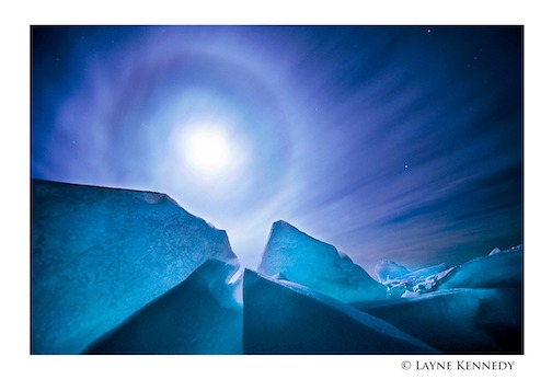 Fast-moving cirrus clouds sprinkle ice crystals across the night sky creating a moon dog by Layne Kennedy.