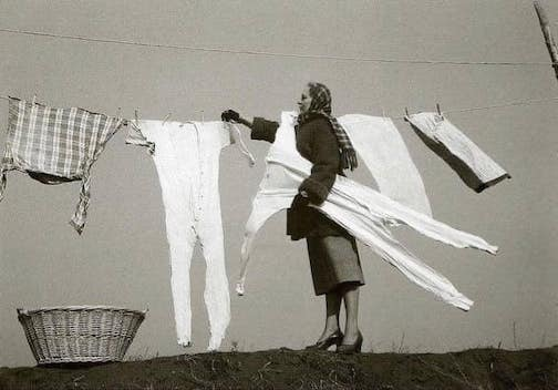 Taking frozen laundry off the line. Photo taken in the 1940s. Photographer unknown.