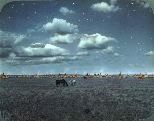 Blackfeet camp at night, Montana, photograph by Walter McClintock, early 1900s, glass lantern slide.