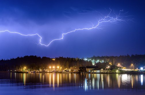 Striking. A lightning bold over Lake Superior and the lights of Grand Marais by Bryan Hansel.