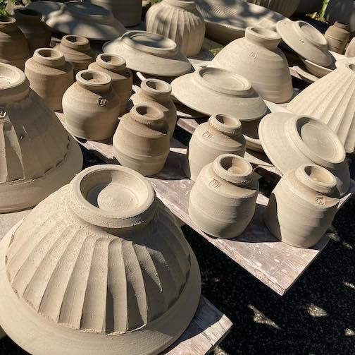 Pottery by Guilermo Cuellar dries in the sun, as he prepares work for the Valley Potters Fall Studio Sale. Click here to learn more.