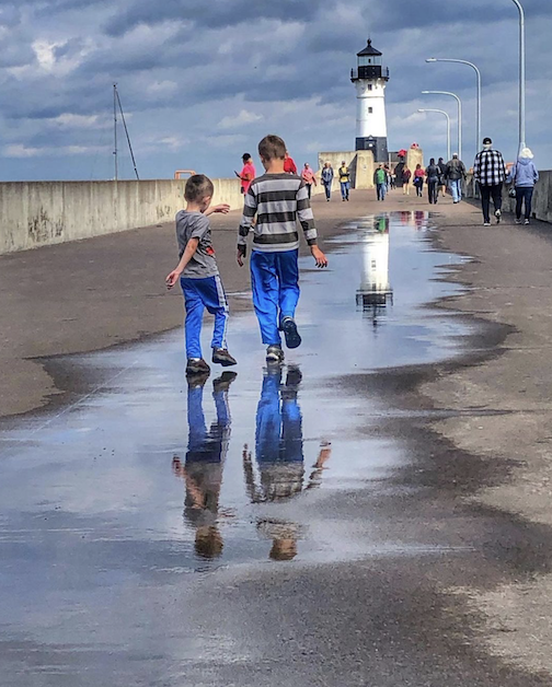 Kids in puddles by Martha Lind.